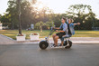 Lovely young couple driving electric bike. Modern city transportation