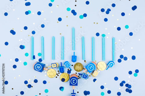 Blue confetti background with menora made of dreidels and chocolate coins. Hanukkah and judaic holiday concept.