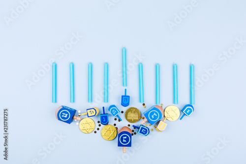 Blue background with menora made of dreidels and chocolate coins. Hanukkah and judaic holiday concept.