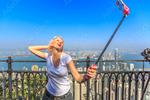 Spoed Foto op Canvas Aziatische Plekken Hong Kong Victoria Peak tourist taking selfie stick picture photo with smartphone enjoying view over Victoria Harbour from viewing platform on top of Peak Tower.
