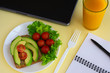Healthy vegetarian snack with avocado, cherry tomatoes and lettuce leaves at workplace. Closed laptop, glass of juice, fork, notebook, pen on yellow background.