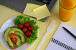 Healthy vegetarian snack with avocado, cherry tomatoes and lettuce leaves at workplace. Open laptop, glass of juice, fork, notebook, pen on yellow background.