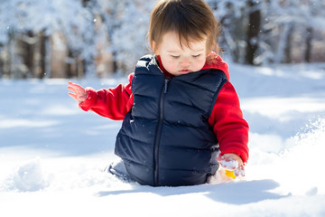 Fototapeta Toddler boy playing in the snow on a winter day