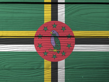 Flag Of Dominica On Wooden Wall Background. Grunge Dominica Flag Texture, Green Field With Cross Of Yellow, Black And White, Sisserou Parrot On Red Disk And Star.