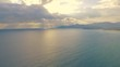 Dramatic aerial view of the sea with rays of light beaming through the clouds above.