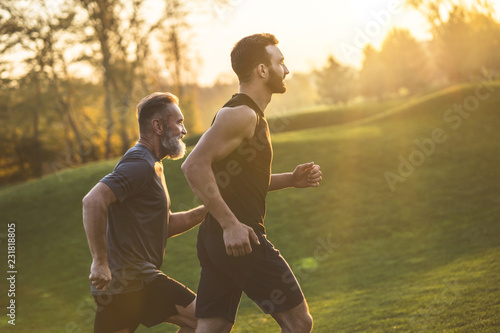 Photo  The two sportsmen running on the grass on the sunny background