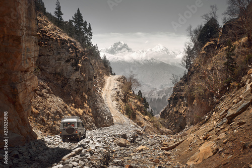 Stampa su Tela Off-road vehicle goes an extreme mountain path during an expedition to Himalayas