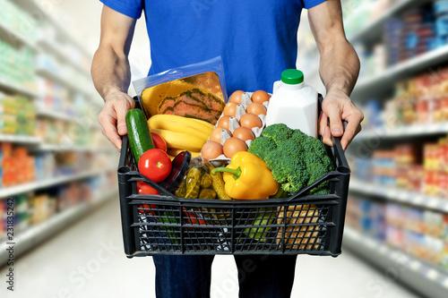 Plakat człowiek z pudełko żywności w ręce w sklepie spożywczym