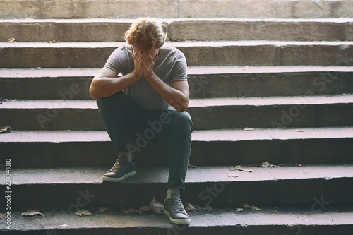 Photo  Stressed young man sitting on stairs outdoors