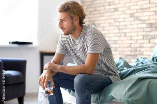 Stickers pour porte Bar Depressed young man drinking alcohol at home