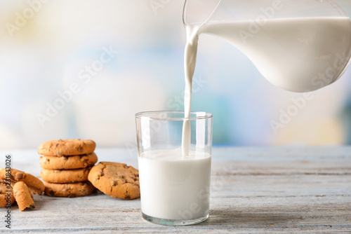 Valokuva  Milk pouring from jug into glass with cookies on wooden table