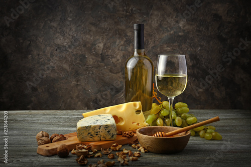 Fototapeta Glass and bottle of white wine with snacks and ripe grapes on wooden table obraz