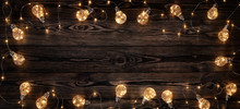 Empty, Dark Wooden Background Illuminated By Retro Light Bulbs, With Copy Space