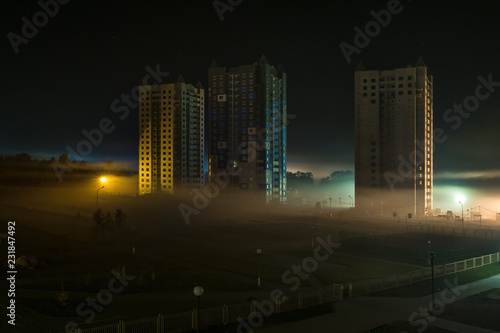 Poster Stad gebouw night panorama of residential area with high-rise buildings in the fog early in the morning