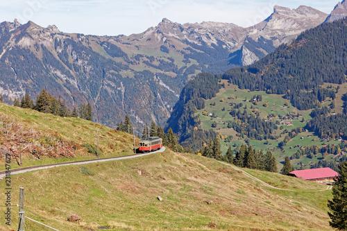Fotobehang Spoorlijn Panoramatic view of Jungfrau Region with incoming train from Gruetschalp (Grütschalp) near Winteregg, Jungfrau Region, Switzerland