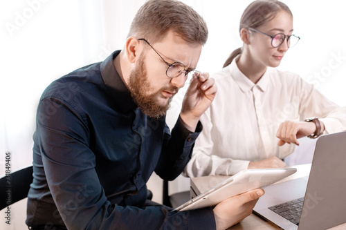 Photo Two young angry business woman man colleagues sit work at white desk with contemporary laptop isolated background