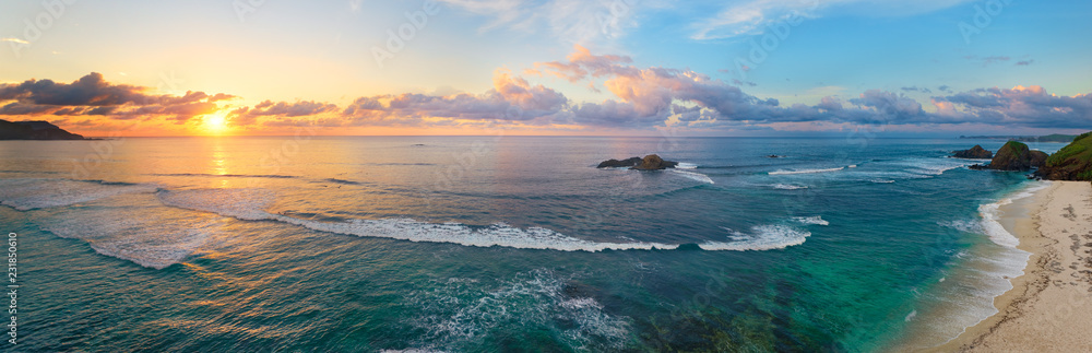 Fototapeta Panoramic view of tropical beach with surfers at sunset.