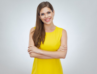 Fototapeta Smiling woman wearing yellow dress standing with arms crossed.