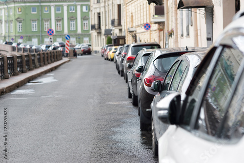 Photo  A number of cars parked in a continuous stream to the right side of the road