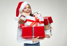 Happy Woman Wearing Santa Hat Holding Pile Of Gifts.