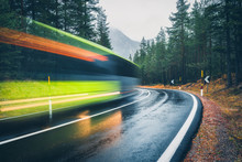 Blurred Green Bus On The Road In Autumn Forest In Rain. Perfect Asphalt Mountain Road In Overcast Rainy Day. Roadway, Pine Trees In Alps. Transportation. Highway In Foggy Woodland. Car In Motion