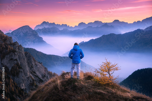 Poster Marron chocolat Sporty man on the mountain peak looking on mountain valley with low clouds at colorful sunset in autumn in Dolomites. Landscape with traveler, foggy hills, forest in fall, amazing sky at dusk in Alps