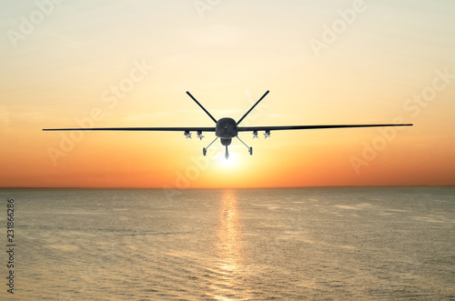 Unmanned military drone patrols the territory at sunset, flying above water surface. The view is straight ahead.