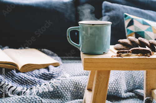 Obraz Cup of hot drink on wooden table. Living room interior with blue sofa on background. Cozy winter or autumn concept - fototapety do salonu