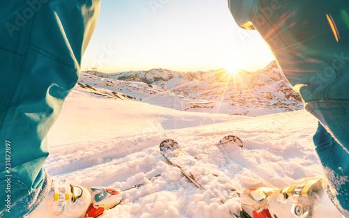 Legs view of skier athlete standing in front of wonderful sunset in ski resort