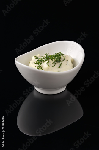 Foto op Canvas Kruiderij Sauce in a white bowl on a black background with reflection.