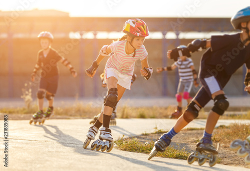 A girl training inline skating with other children Fototapeta