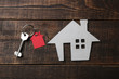 The concept of buying a home. Decorative house with keys and keychain on a blue wooden table. top view