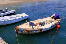 Small Boats Moored At A Wooden Jetty On A Bright Blue Sea - One Of Them Is Very Old And Patched With Rusty Metal Plates
