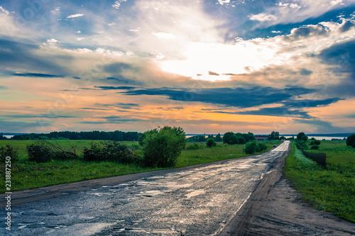 Fotografie, Obraz  A wet asphalt road leading to Lake Pleshcheyevo in the rays of the setting sun