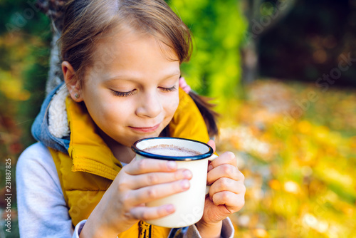 child girl drinking chocolate from a cup dressed in a warm yellow vest in autumn scenery