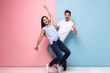 Leinwanddruck Bild - Full length image of optimistic man and woman in casual wear laughing and having fun together, isolated over colorful background