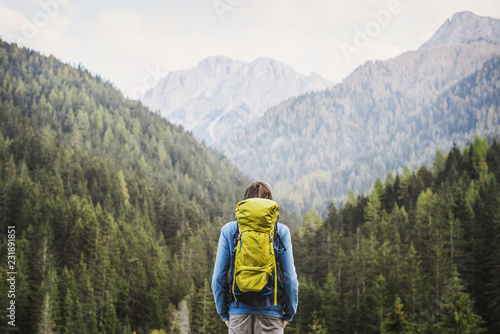 Vászonkép Young backpacking man traveler enjoying nature in Alps mountains