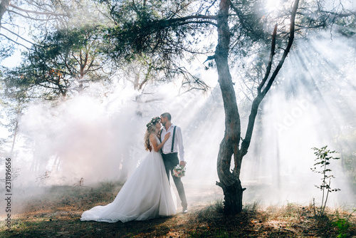 Valokuva bride and groom on the background of fairy fog in the forest