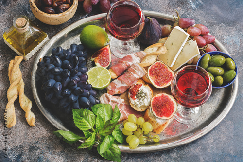 Fotografía  A variety of appetizer, prosciutto, grapes, wine, cheese with mold, figs, olives on a metal tray