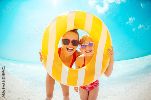 mother and child looking through yellow inflatable lifebuoy
