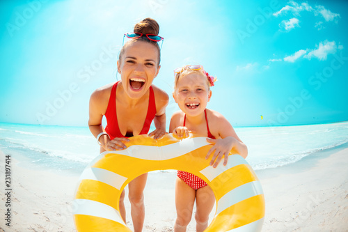 happy mother and daughter holding yellow inflatable lifebuoy
