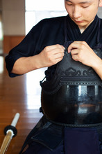 Male Japanese Kendo Fighter Kneeling On Floor, Fastening His Breastplate.