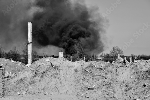 Fototapety, obrazy: A pile of concrete rubble with protruding rebar on the background of thick black smoke in the sky. Black and white