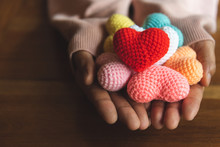 Mixed Colors Yarn Heart On Giving Hands. Close Up Of Colorful Handmade. Heart Donation Concept. Valentine  Love Forever Theme