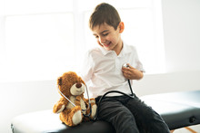 A Doctor Boy Playing And Cure Bear At The Pediatric