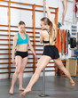 Woman exercising pole dance with trainer
