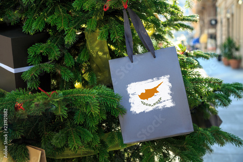 Poster Cyprus Cyprus flag printed on a Christmas shopping bag. Close up of a shopping bag as a decoration on a Xmas tree on a street. New Year or Christmas shopping, local market sale and deals concept.