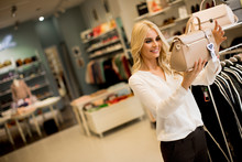 Young Woman Buying Purse In Th...