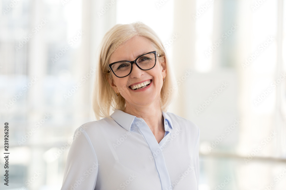 Fototapeta Portrait of smiling middle-aged businesswoman in glasses look in camera making headshot picture, happy mature female employee pose for picture in office, confident woman excited for new opportunities