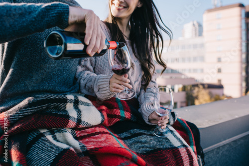Photo cropped shot of young couple covering in plaid on rooftop and pouting red wine i